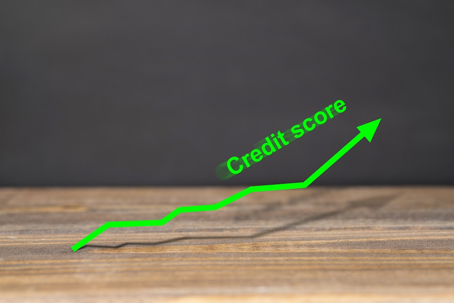 Green upward trend graph shows excellent credit score on wooden surface with black background. Business and financial concept.